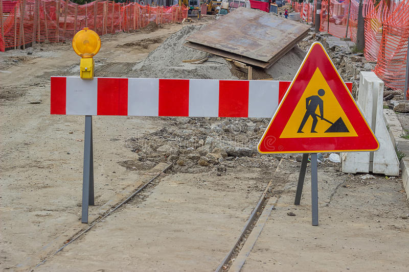 Road construction sign with yellow warning light. And construction barrier stock photography