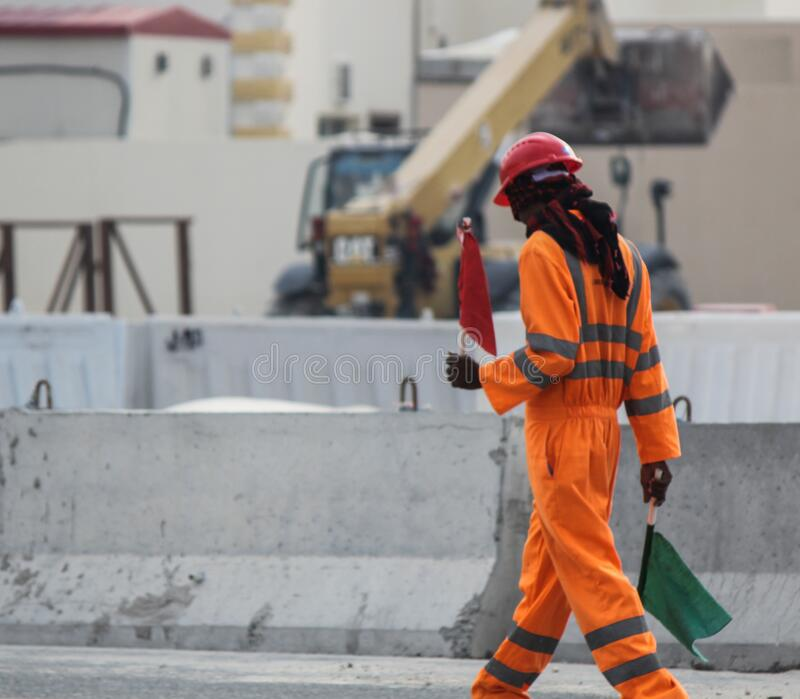 Road Construction Signal Man Helping Heavy vehicle on the road with red and green flag.  stock photo