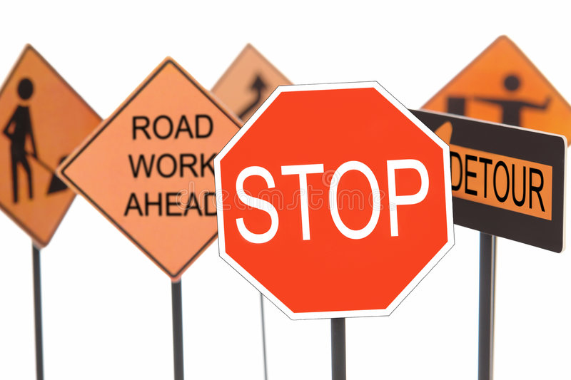 Road construction signs. Closeup of stop sign with various american road construction signs in the background royalty free stock image