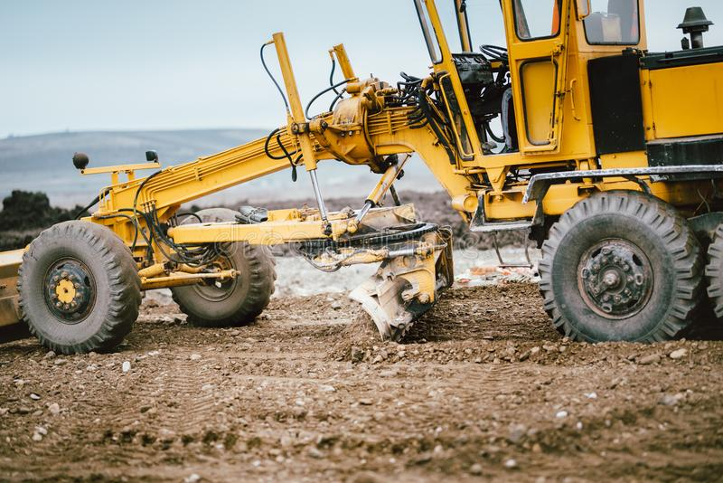 Highway construction site development with motor grader moving earth, soil. Road construction site development with motor grader moving earth, soil stock images