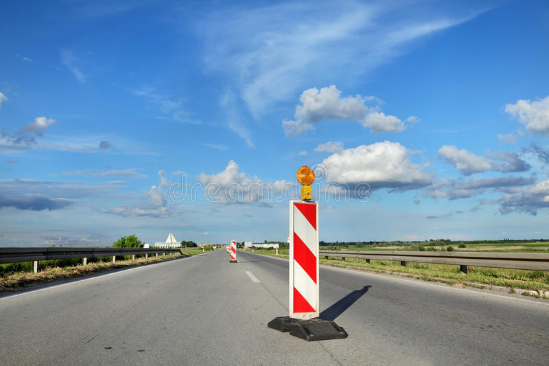 Road construction site. Roadworks, road sign in a highway on reconstruction with blue sky and clouds stock photo