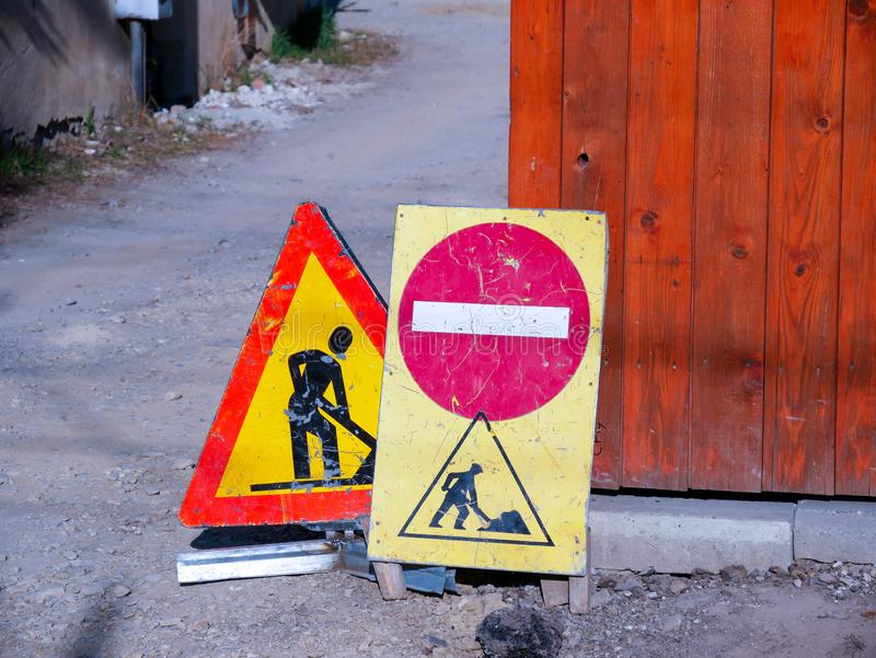 Road construction street signs close up shot. Near a wooden fence stock images