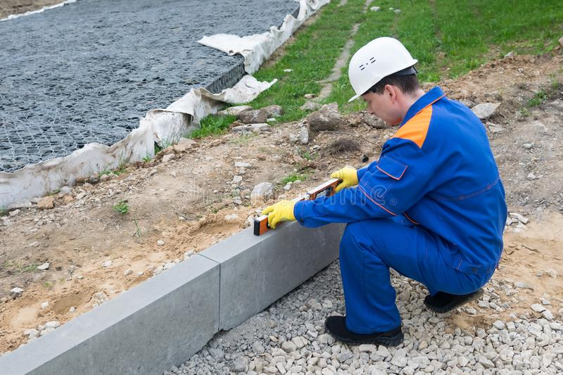Road construction worker measures road slope level royalty free stock image