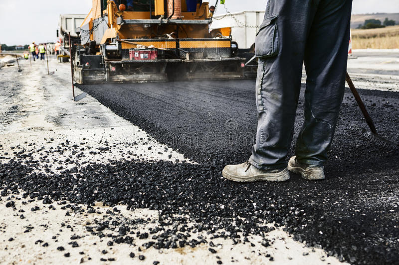 Road Construction. Worker operating asphalt paver machine during road construction and repairing works royalty free stock photo