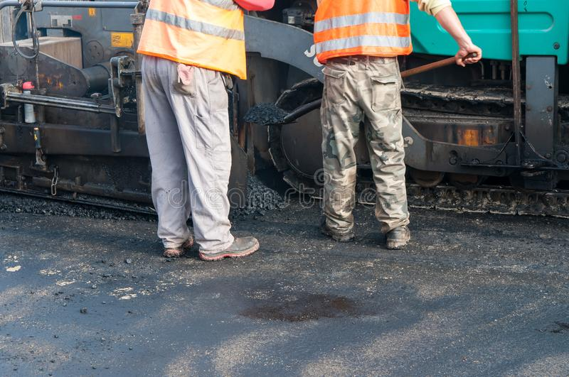 Road construction workers, asphalting machinery. stock photography