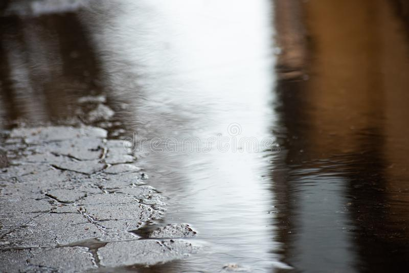 Road in the cracks and puddles stock image