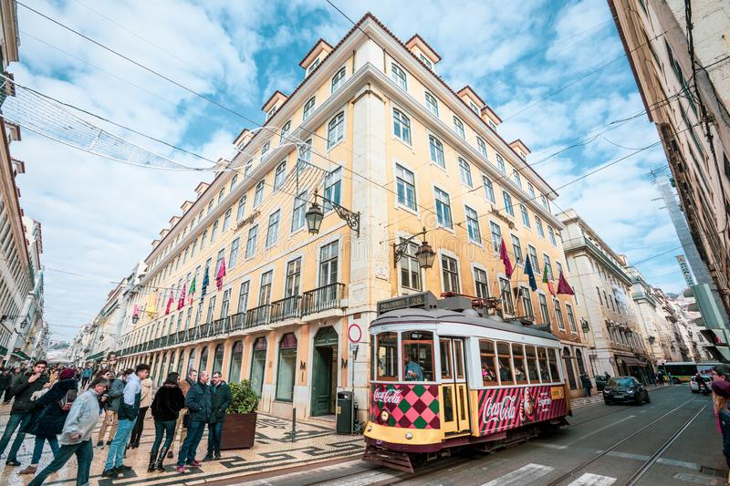 Road crossing between historic palaces of Lisbon, red tram runs through the city. royalty free stock photo