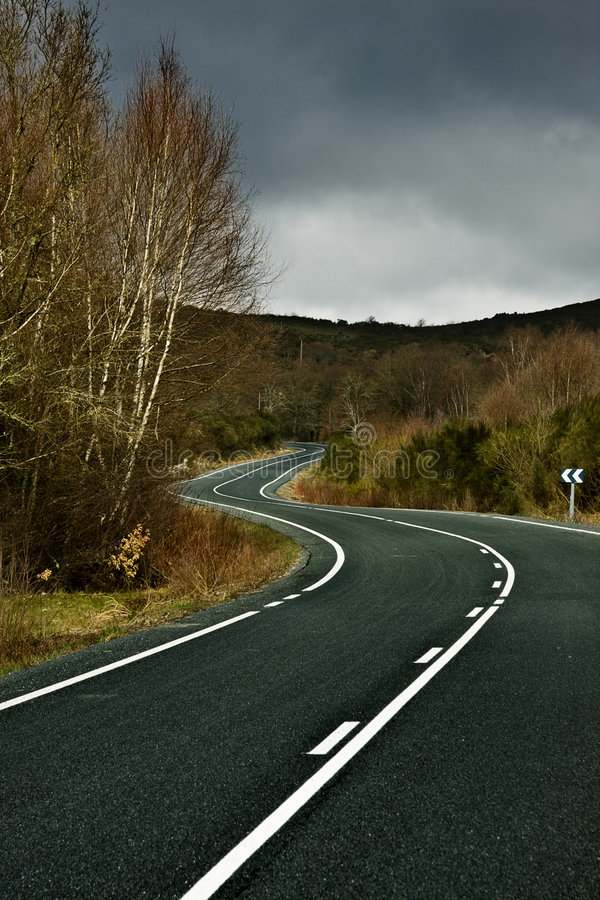 Road curves between nature and the mountains royalty free stock images