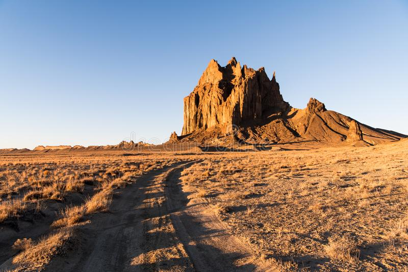 Road curving through a vast landscape to the rock formation of Shiprock in New Mexico stock image