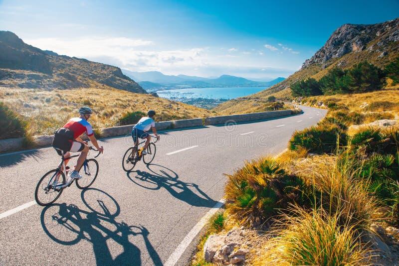 Road cycling-foto Twee triatleettreinen in mooie natuur Zee en bergen op de achtergrond Alcudia, Mallorca, Spanje stock afbeelding