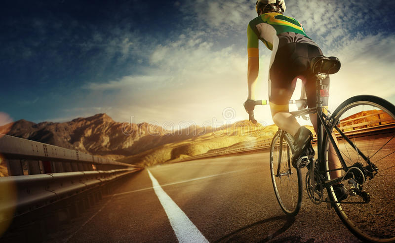 Road cyclist. Cyclist, ride on the road in mountain. Sunset landscape royalty free stock photos