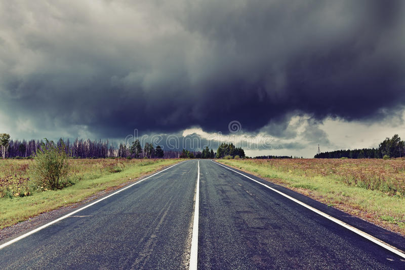 Road and dark thunder clouds. Asphalt road and dark thunder clouds over it royalty free stock photos