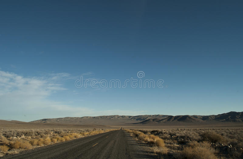 Road through Death Valley National Park. View of a straight section of the park road in Death Valley National Park, California. There is arid desert`s vegetation stock photos