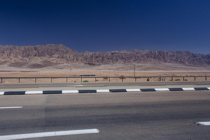 Road in the desert in the Israil in sunny day with view to red iordan mountains and blue sky stock photo