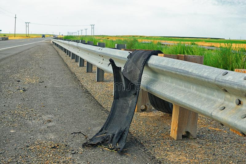 Tread from a truck tire hanging over a guard rail. With the road disappearing into the distance in a rural country setting, one gets the idea of the force at stock images