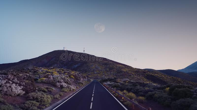 Road at dusk among the frozen volcanic lava of the volcano Teide Tenerife. Volcanic road in the dusk among the lava of the volcano Teide, Tenerife stock photo
