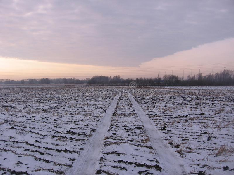 The road through the empty field, the traces of the car. Road through freeze the empty field car tracks evening landscape hard to drive stock images