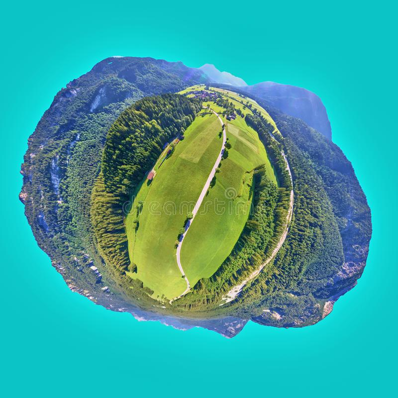 Road in front of a meadow and a forest at the edge of the Alps, Little Planet, Spherical 360 degrees seamless panorama view in royalty free stock photography