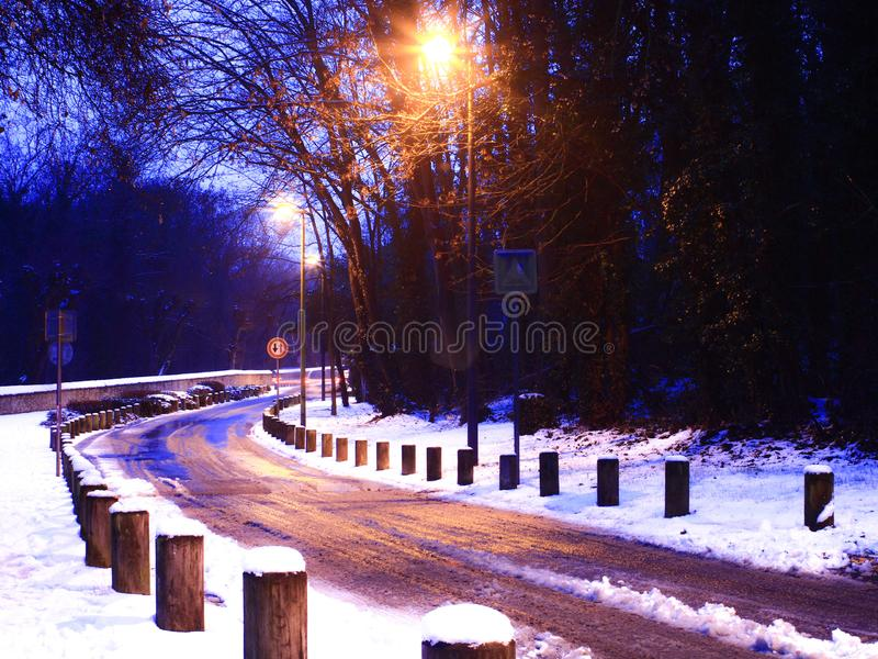 A road full of snow at night with lampposts. A path delimited by wooden blocks at the edge of a snowy forest with road signs stock photos
