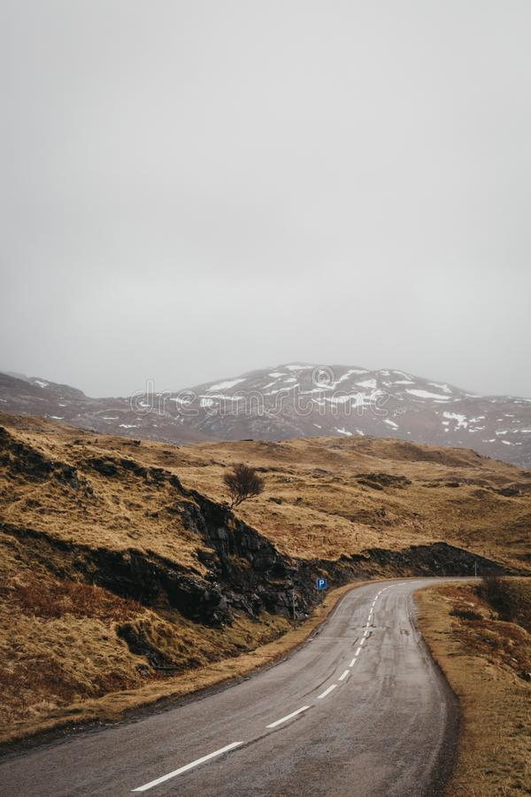 Road going through Scottish Highlands near Lochinver. Road going through Scottish Highlands near Lochinver on a foggy spring day royalty free stock photography