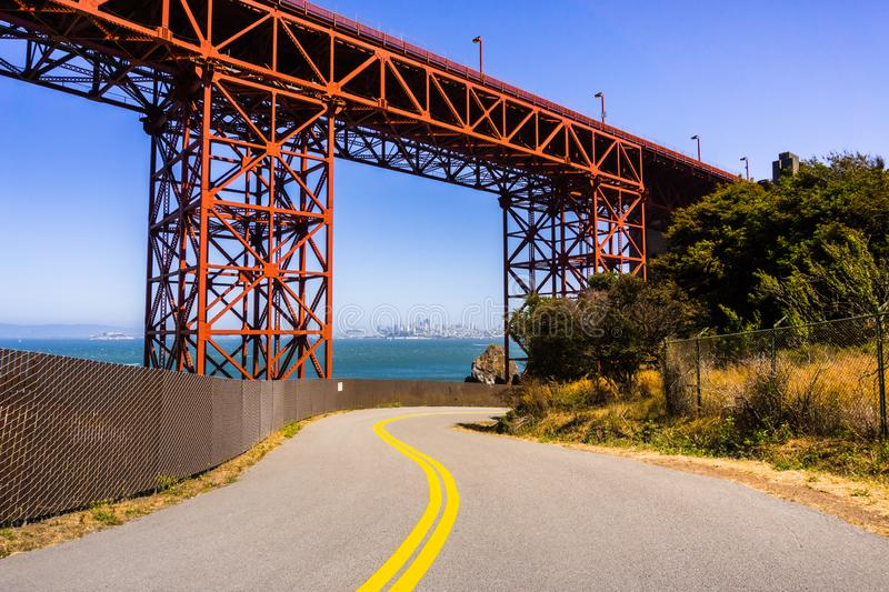 Road going under Golden Gate Bridge, the San Francisco skyline visible in the background; California stock photo