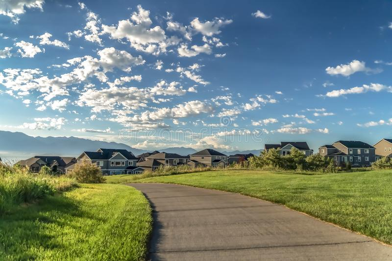 Road on a grassy terrain that leads to houses with view of lake and mountain. Blue sky and puffy clouds can be seen over the landscape on this sunny day royalty free stock photos