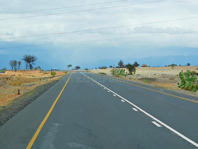 The road of happiness. Cloudy sky in Tanzania, Yellow earth in Africa, Africa, to meet adventures, safaris, Tarangiri, drought, Ngorongoro,gray earth, the royalty free stock image