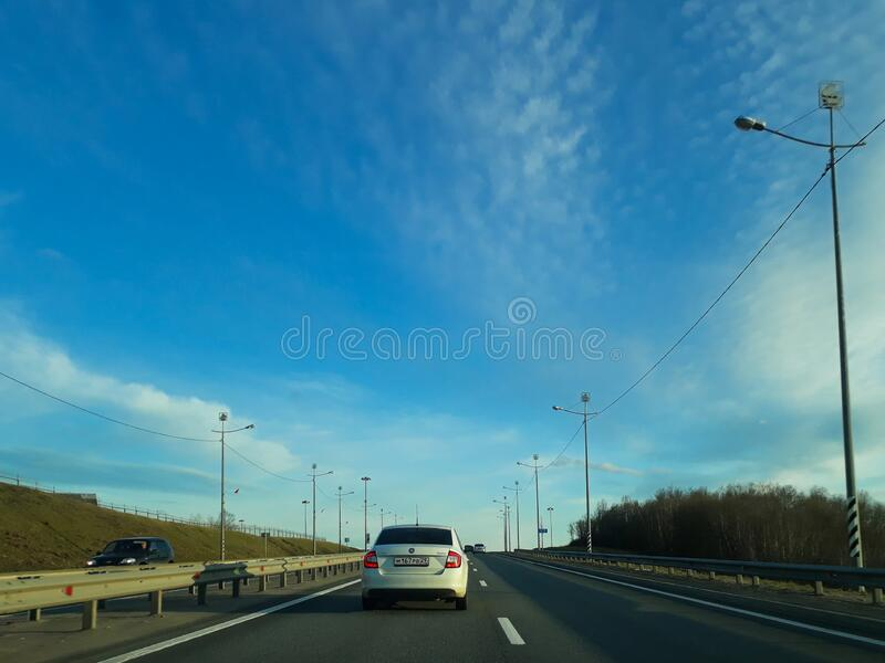 A road or highway leading to the horizon. View from the car window. Northern dim summer, blue sky with white clouds stock image