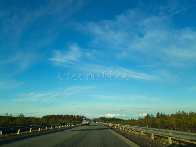 A road or highway leading to the horizon. View from the car window. Northern dim summer, blue sky with white clouds royalty free stock image