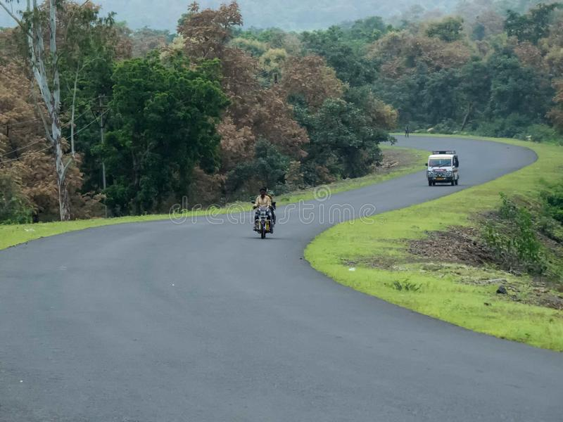 Road/Highway through lush green jungle forest. Road/Highway through lush green forest area in India in monsoon season.  No traffic road with only two vehicles stock photography