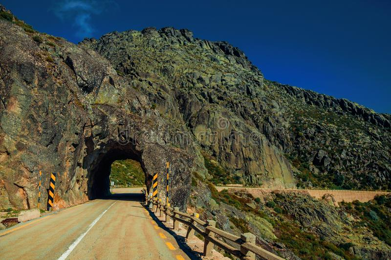 Road on rocky landscape passing through tunnel royalty free stock photos