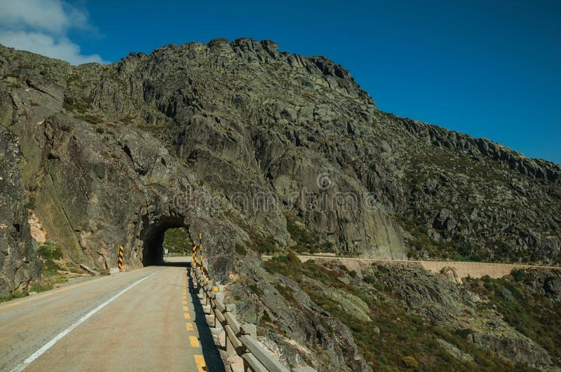 Road on rocky landscape passing through tunnel stock photo