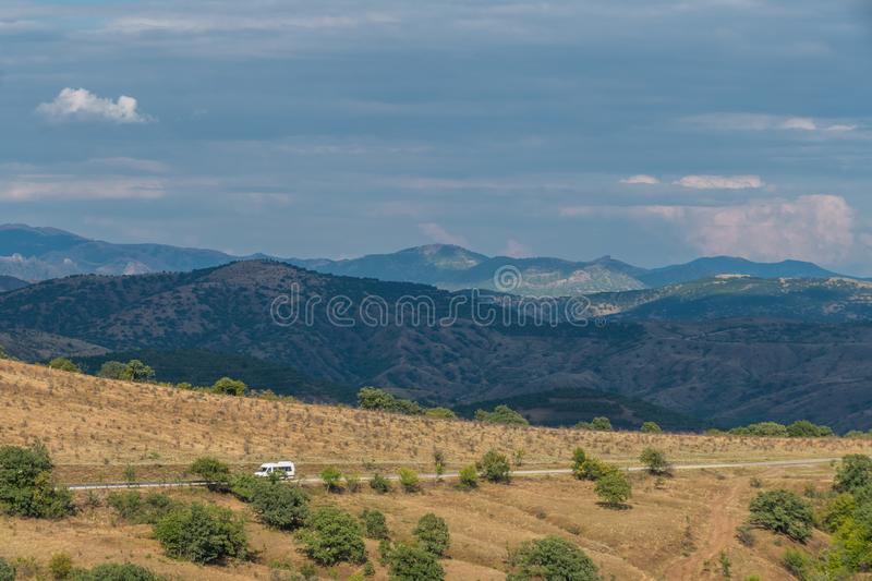 Country road through hilly terrain. Road through hilly terrain on background of blue mountains and gray clouds royalty free stock image