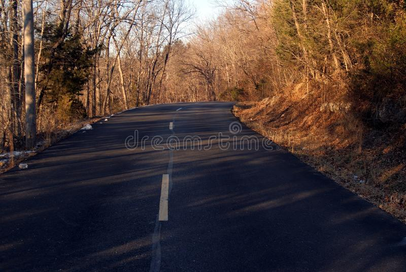 The Road Home I - Asphalt Highway in Bronze Late Afternoon Winter Sunlight. stock photography