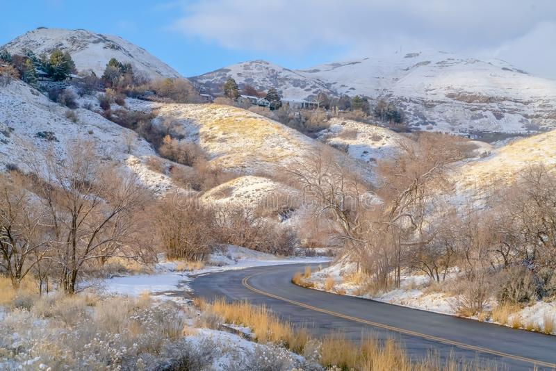 Road and homes on sunlit snowy mountain in winter. Road curving through the snowy mountain in Salt Lake City on a sunny winter day. Homes and blue sky with royalty free stock photo