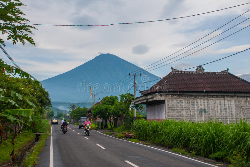 The road with houses in Amed. Views of mount Agung in cloudy weather. Bali royalty free stock photos