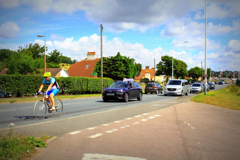 A259 road Hythe Kent United Kingdom. Mature man cycling and vehicles driving after him on A259 coastal road in Hythe town Kent England United Kingdom on nice stock image