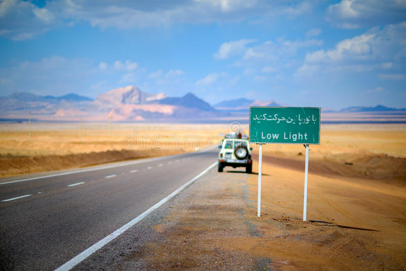 The road in Iran. Road signs in Iran, are written on Farsi, around stony brightly orange desert, mountains and the blue sky are expensive, the car costs at the royalty free stock image