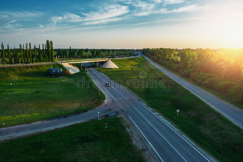 Road junction of speedy country highway route among green fields and trees with fast moving cars and trucks on. Background of beautiful dramatic sunset in warm stock photos