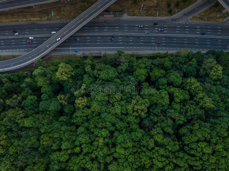 Road junction top view. Highways and forest. Traffic in the city. Aerial view. stock photos