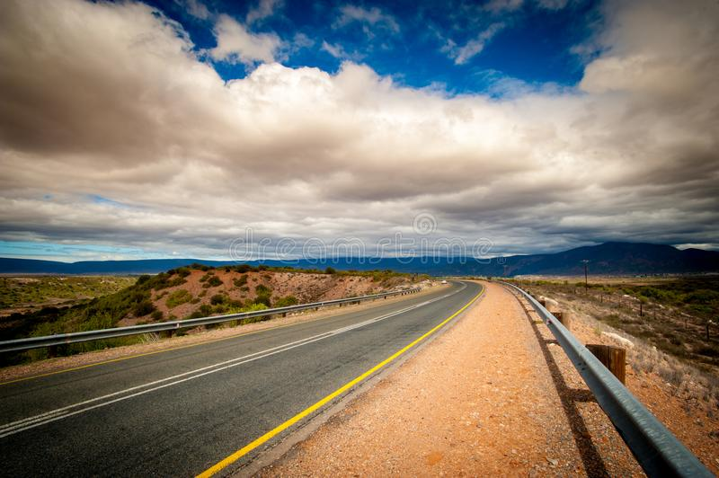 Road - Klein Karoo desert - Oudtshoorn - South Africa. Road - Oudtshoorn - South AfricanOut Oudtshoorn, Klein Karoo desert, the road makes a beautiful curven royalty free stock photography