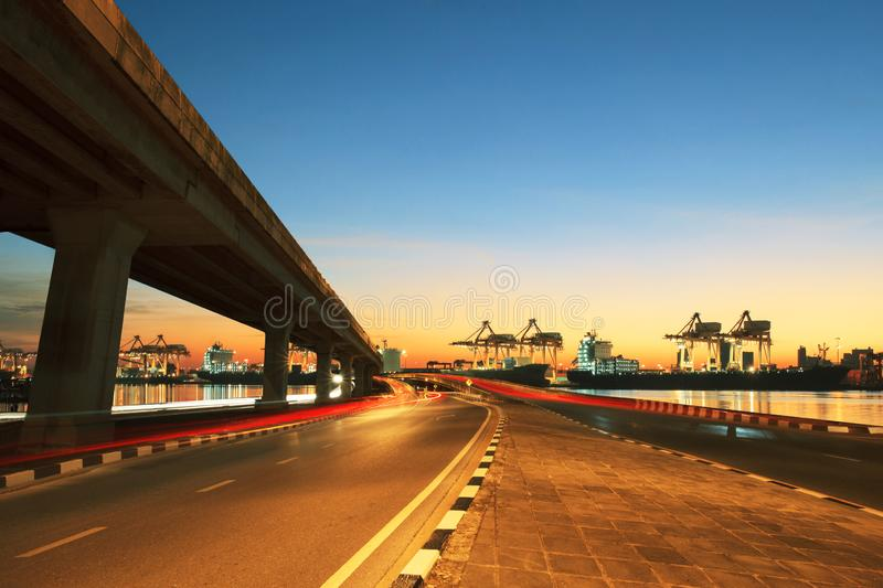 Road ,land bridge run into ship port and commercial cargo plane flying above use for land ,air and vessel transport industry. Business royalty free stock image