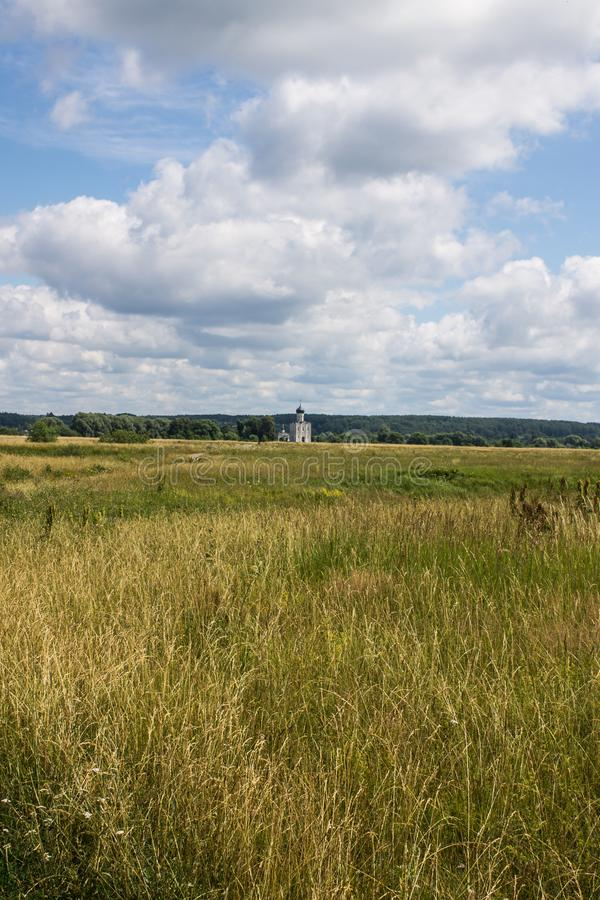 The road leading through the meadow to the Church of the Intercession on the Nerl summer day stock photo