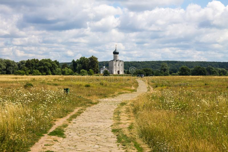 The road leading through the meadow to the Church of the Intercession on the Nerl summer day stock photography