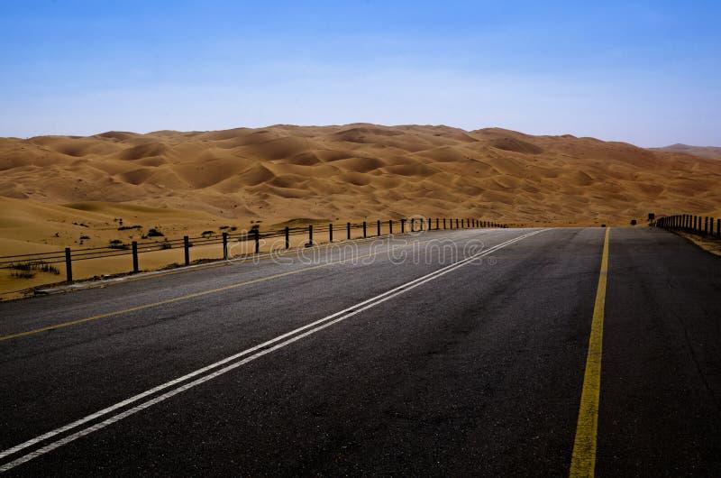 Road leading through sand dunes in the desert of Liwa Oasis United Arab Emirates. Desolate road winding through the sand dunes of Liwa region near Abu Dhabi UAE stock photos
