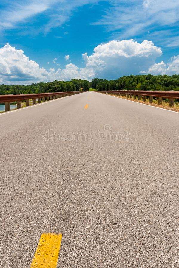 Road leading straight to the horizon. Empty straight road line. Road leading straight to the horizon. Empty american country road between lake and forest royalty free stock photo