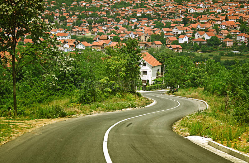 Road leading to town. Winding countryside road leading down to town royalty free stock photos