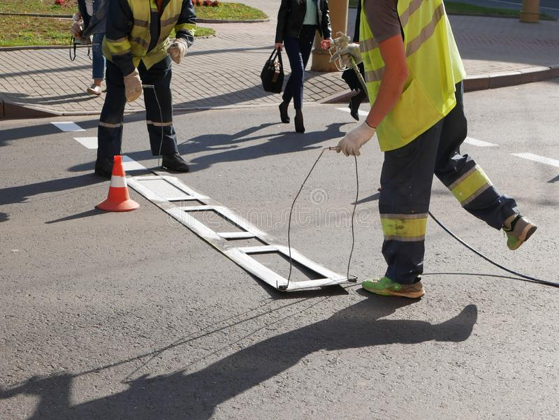 Road marking. Drawing a road marking. spraying in road construction. Worker draws a white line on the surface of the street royalty free stock photo