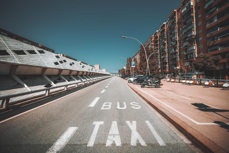 A road with marking and inscriptions. A wide-angle view of the road in a European city with inscriptions `BUS` and `TAXI` on one lane, soundproof wall, parking royalty free stock photo
