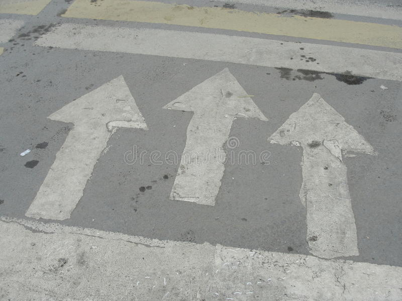 Road markings. arrows showing the direction of movement at the intersection crosswalk. Three white arrow road markings. Three white arrow road markings on royalty free stock photography